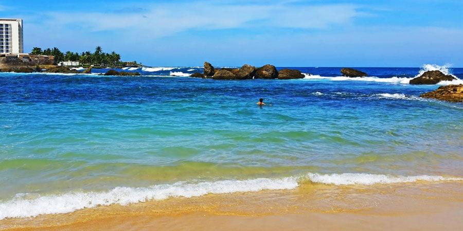 View of a person swimming in Condado Beach in San Juan