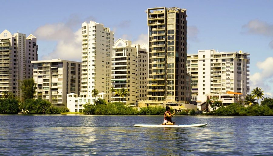 View of a woman enjoying paddle boarding in the lagoon and the tall buildings from the background