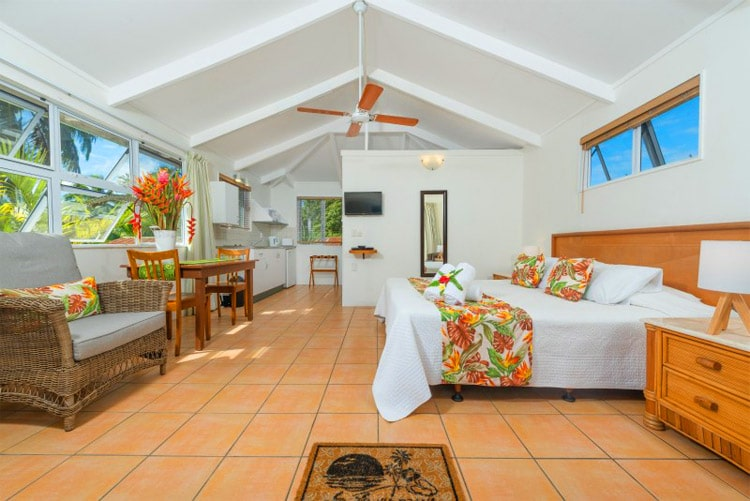 room of a villa with bed and ceiling fan and other fresh furnitures