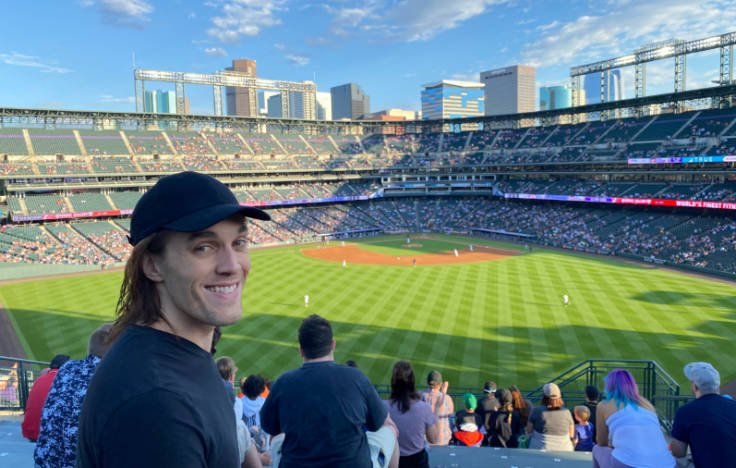 Nate with Coors Field and Denver skyline in background