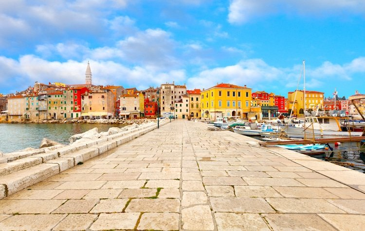 The view of an old town in Croatia with brightly colored buildings and a stone walkway