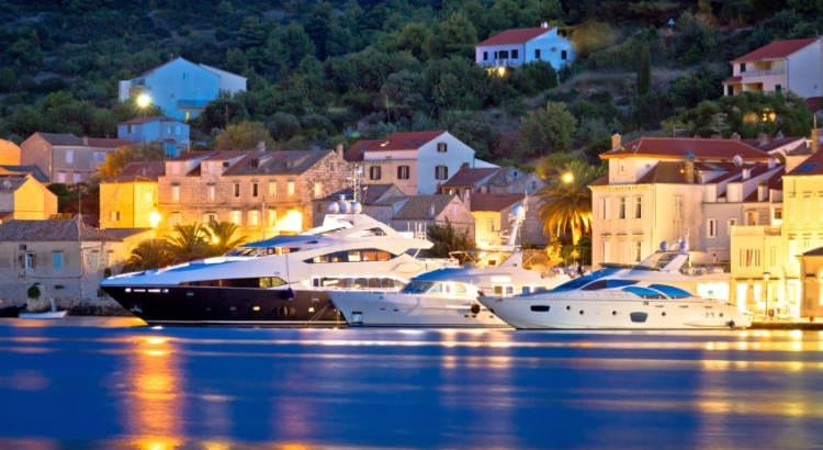 three yachts on blue water on a dark night in Vis