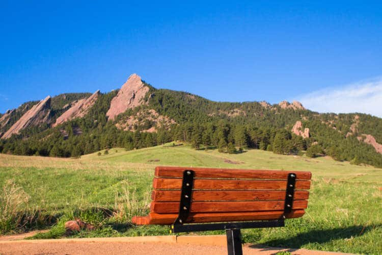 A bench in front of the Boulder Flatirons