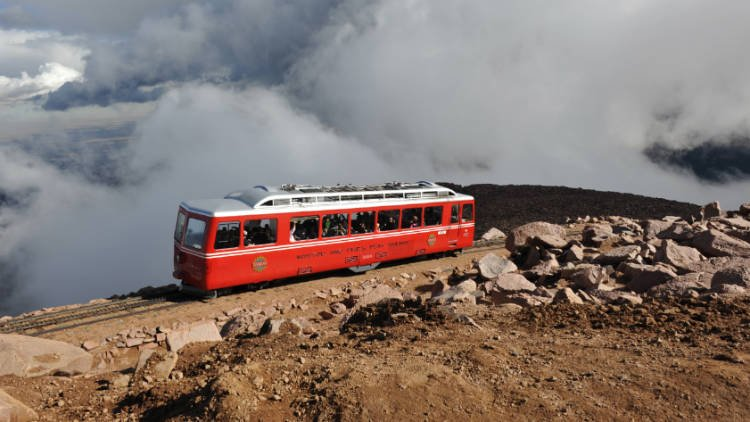 A red tram climbs Pikes Peak