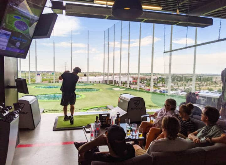 A golfer swinging at a ball at Thorton's Top Golf location