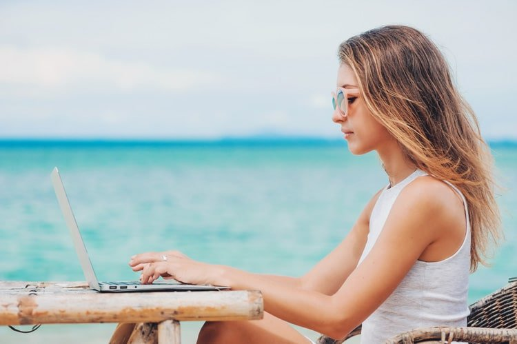 woman with laptop with sea on background