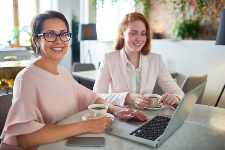 Two business women talking with laptop and coffee