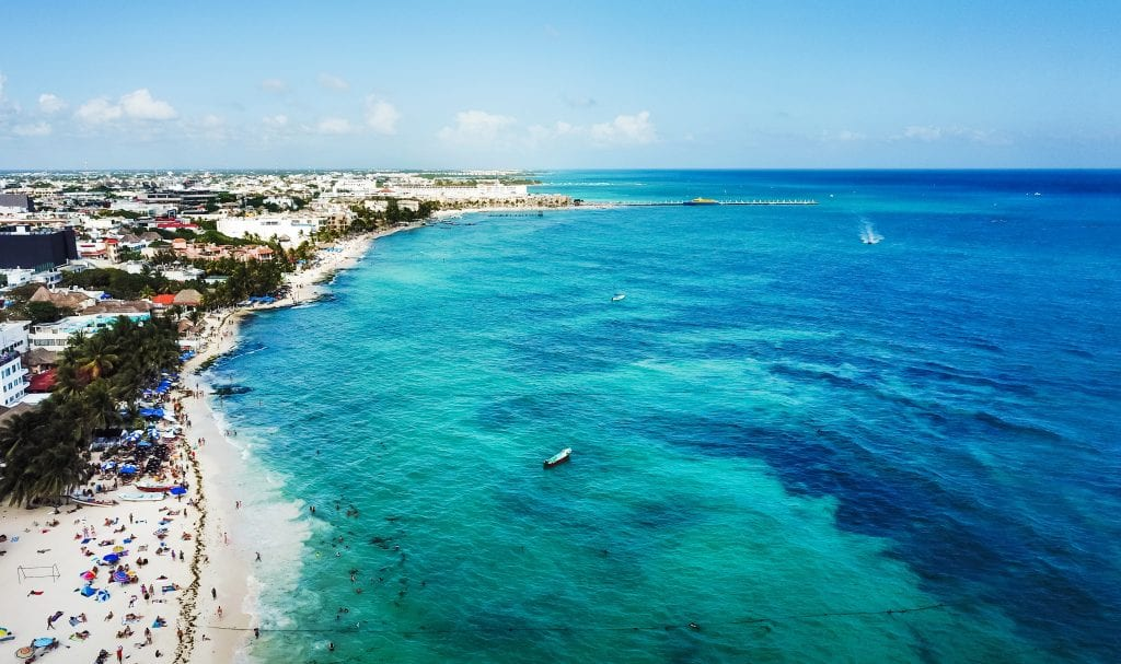 An overhead drone photo of the water, beach, and town of Playa del Carmen, Mexico