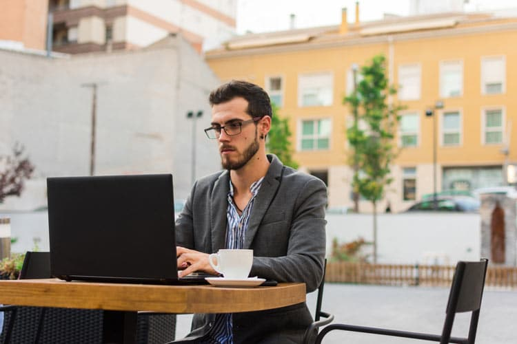 man working on laptop in a bar terrace