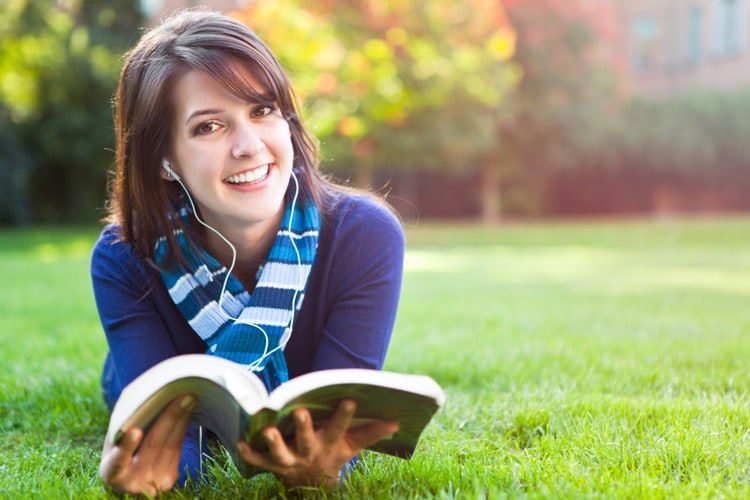 smiling woman reading book on grass
