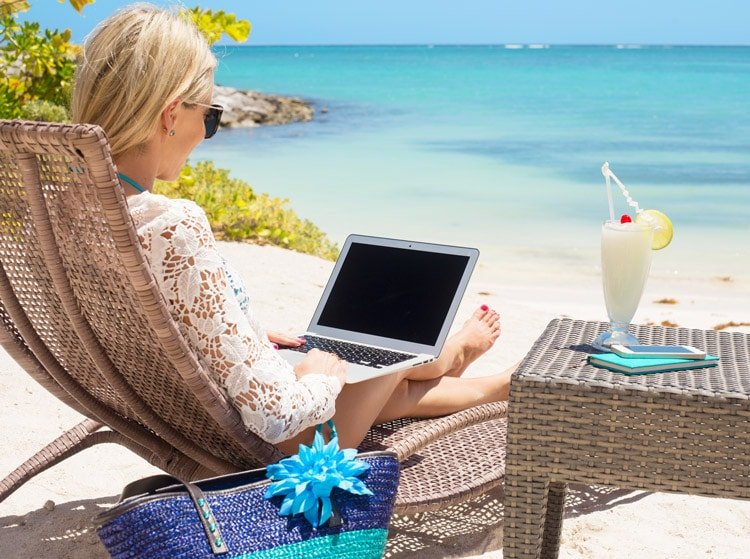 Business woman working with computer on the beach