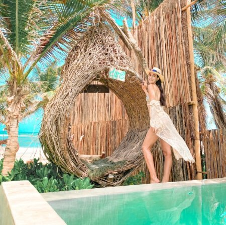 Clara standing next to the nest at the pool at Tulum's Dune Boutique Hotel