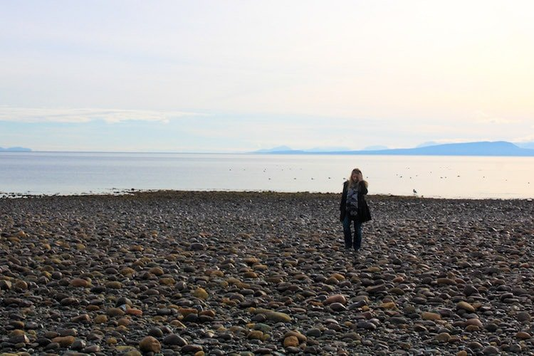 Taylor walks along the pebby beach of eastern Vancouver Island