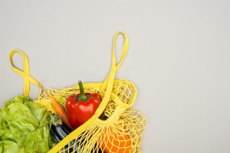 Yellow string bag with fresh ripe vegetables
