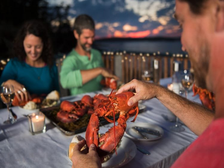 three people eating lobster for dinner with sea in background