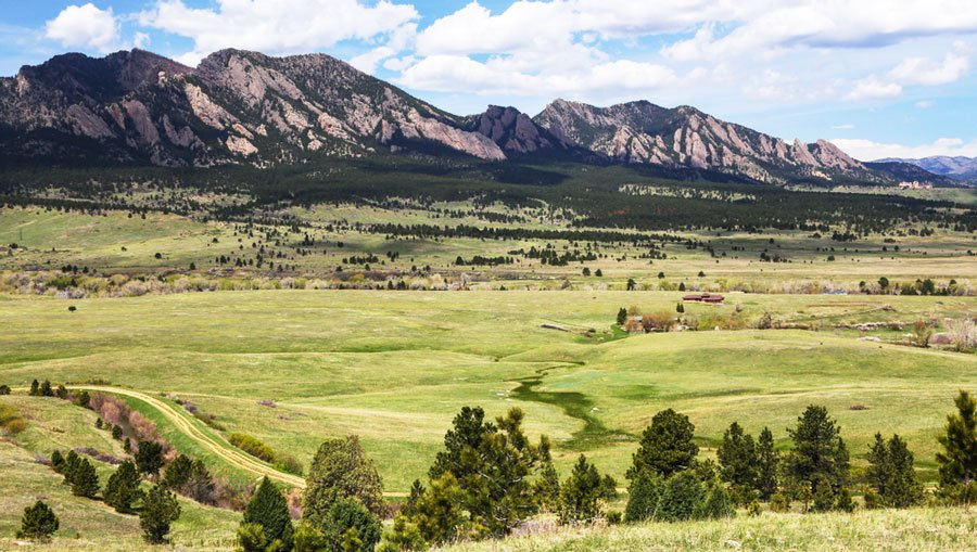 View of the Flatirons Vista Trail and a wide grass field