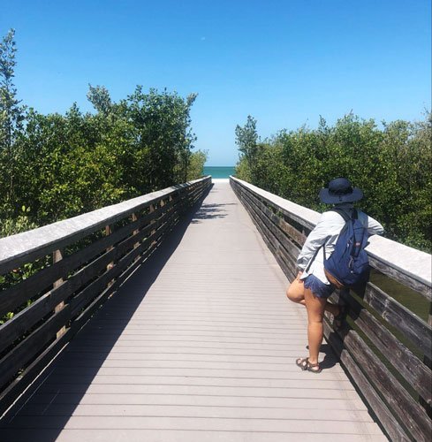 View of a lady standing in the walkway going to the beach
