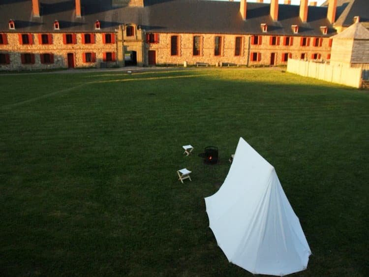 white tent on a green flat grass and a building on background