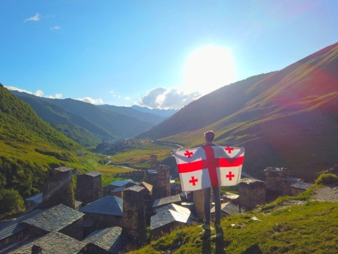 Travel Lemming blogger with Georgia Flag looking out over Ushguli Svaneti