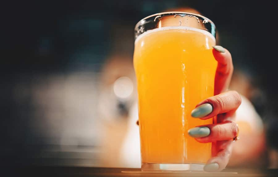 View of a woman's hand holding a glass of beer