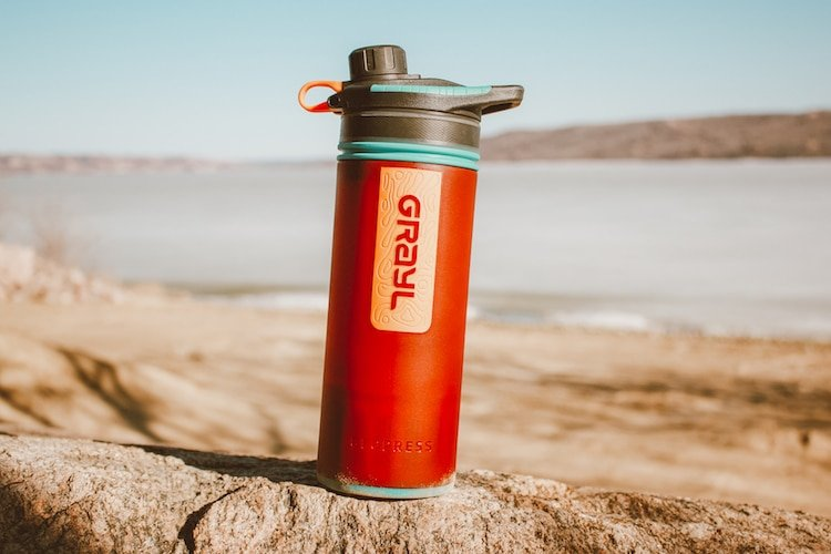 A Grayl Water purifier sits on a rock in front of a beach and a frozen-over lake