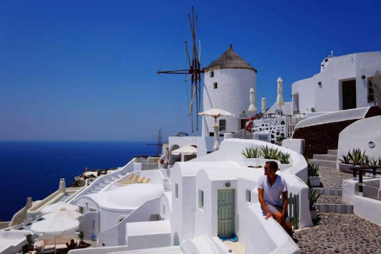 The author looking out over a vista of windmills and houses in Santorini