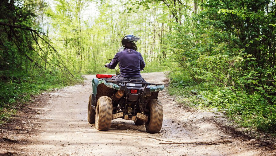 View of a man riding an ATV in the mountain road