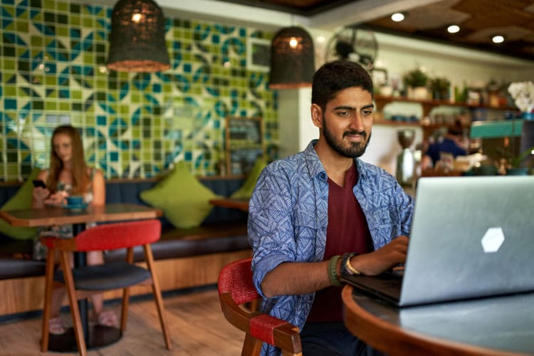man working on laptopn in trendy cafe
