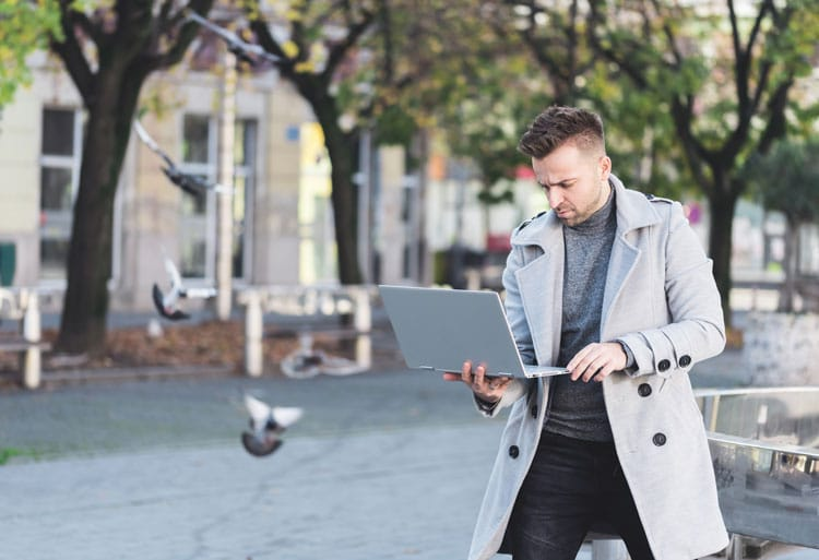 man with coat holding laptop while walking