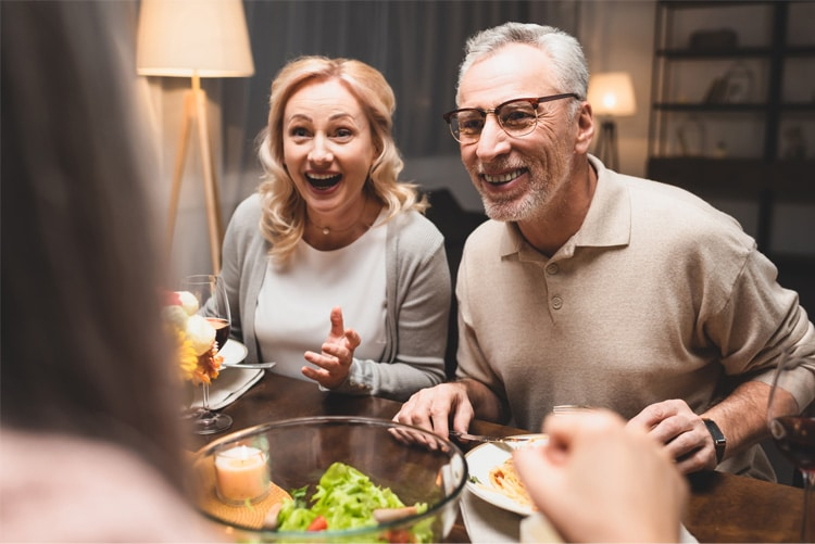 man and woman with big smiles on their faces while conversing with a friend during dinner