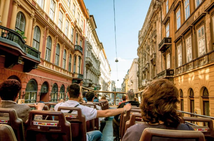 View of passengers on top of a bus surrounded by buildings in downtown Budapest
