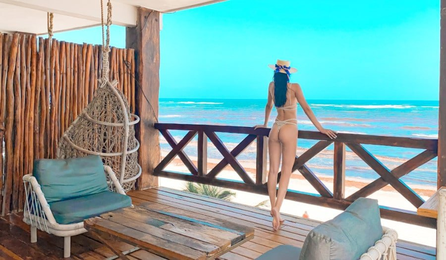 Clara standing on a hotel balcony looking out at Tulum Beach