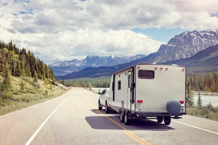 A truck hauls a camper along the Icefields Parkway in Alberta, Canada, surrounded by mountains and lakes.