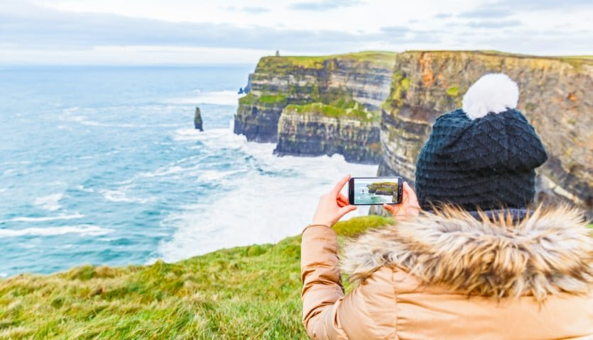 Woman taking a photo of the Cliffs of Moher