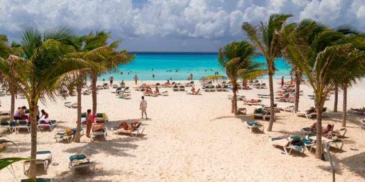 Playacar beach in Playa del Carmen lined with palm trees and filled with people.