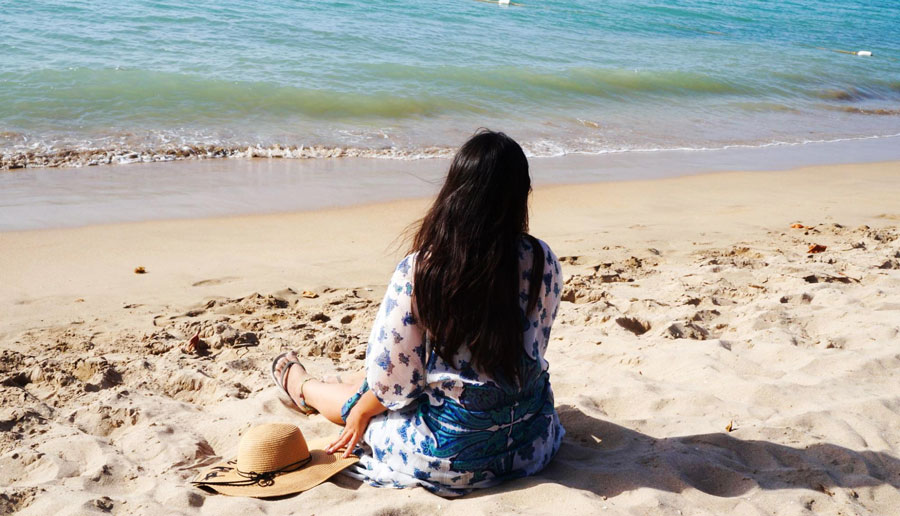 View of the author sitting on the sand by the beach in Isla Verde