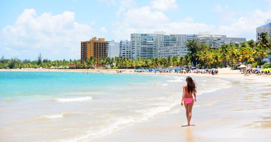 View of a woman walking along the shore in Isla Verde