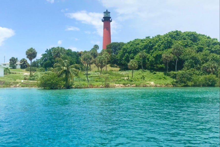 View of lighthouse at Jupiter with water in foreground