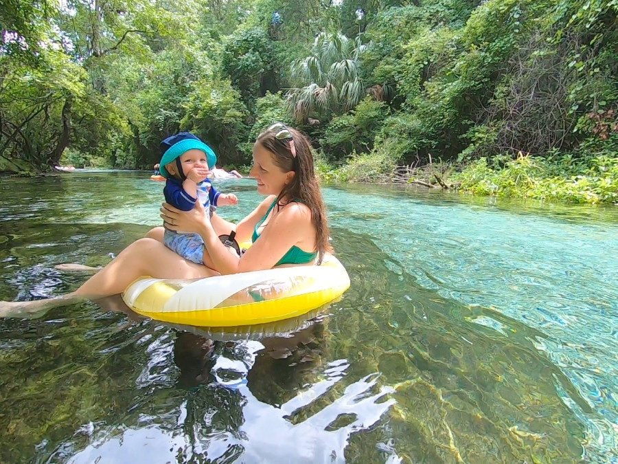 View of the author holding her child in a float on the river at Kelly Park Rock Springs