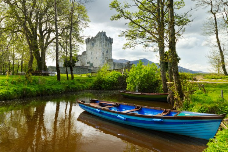 A boat in front of Ross Castle in Killarney