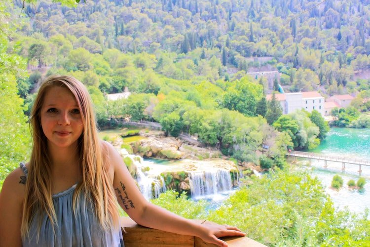Taylor stands in front of a view of Krka National Park, with boardwalks, lakes, and waterfalls