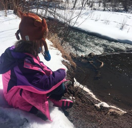 View of the author's daughter sitting in a snow in Bear Creek Trail