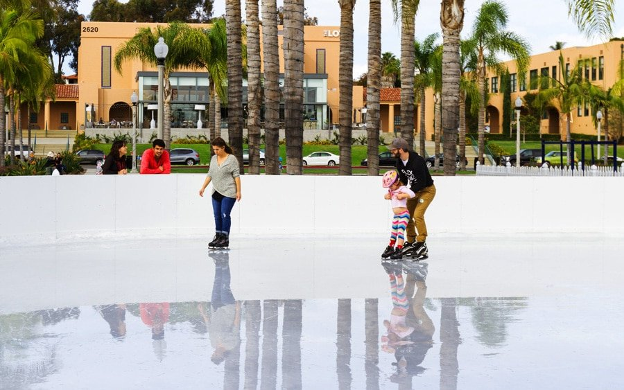 View of a father teaching his daughter how to ice skate