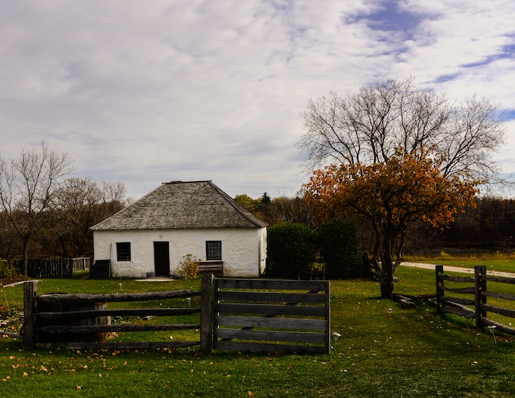 An old white house sits on the Lower Fort Garry National Historic Site in Manitoba