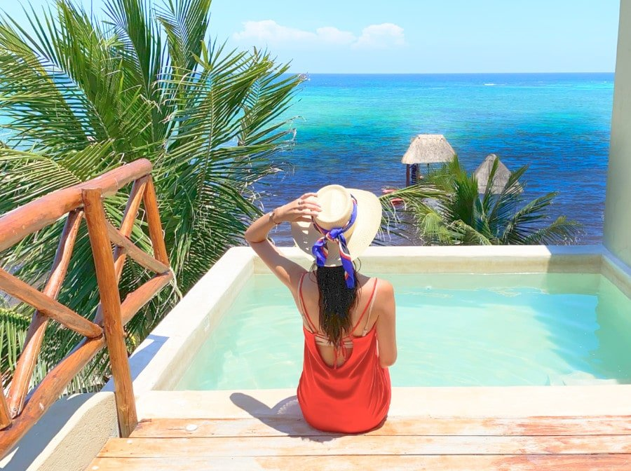 Woman with a hat on a private plunge pool facing the Caribbean sea at Mereva Tulum