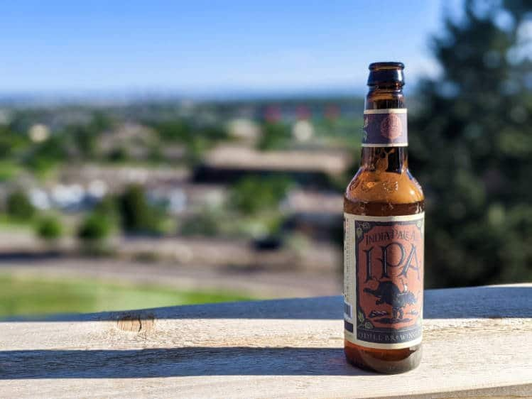A bottle of Odell craft beer against a green backdrop