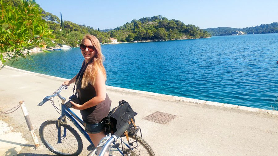 View of the author with her bike and a blueish water on her background