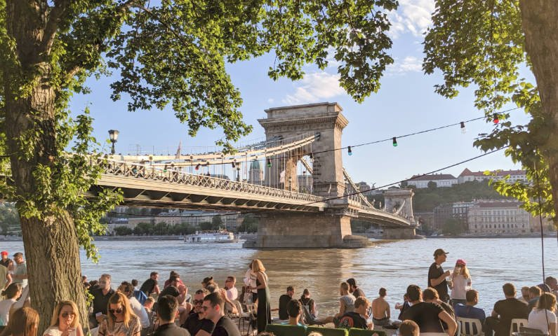 View of the Chain Bridge in Budapest with a crowd at Pontoon bar in the foreground