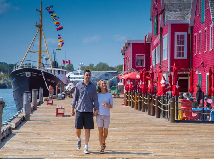 couple walking along the boardwalk with red buildings in Lunenburg