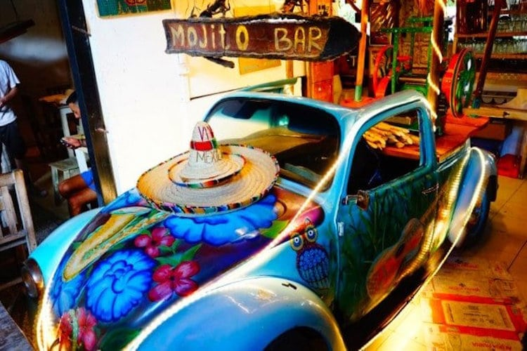 """A small painted car is inside a restaurant with the sign """"Mojito Bar"""" in Tulum, Mexico"""